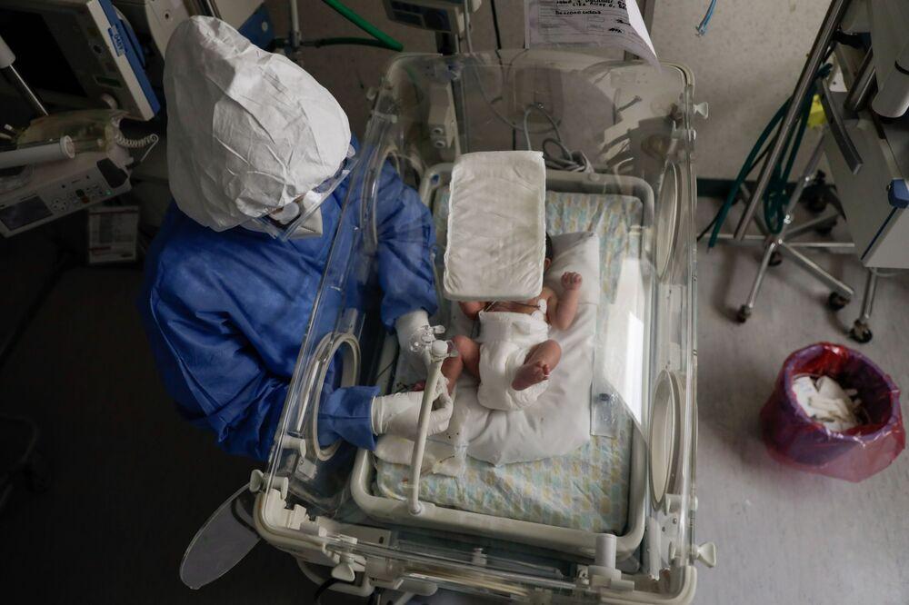 ممرضة تفحص مولودًا جديدًا مصابًا بمرض فيروس كورونا (كوفيد-19)، وهو يرقد في وحدة لحديثي الولادة بفيروس كورونا في مستشفى مونيكا بريتليني ساينز في تولوكا، المكسيك، 4 فبراير 2021