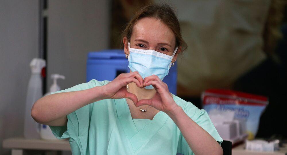 سيلفيا أليخاندرا جيلفيز، طبيبة الطوارئ في عيادة كولومبيا، تصنع إشارة القلب بيديها قبل تلقيها حقنة بجرعة من لقاح فايزر ضد كوفيد-19 في عيادة كولومبيا في بوغوتا، كولومبيا، 18 فبراير 2021