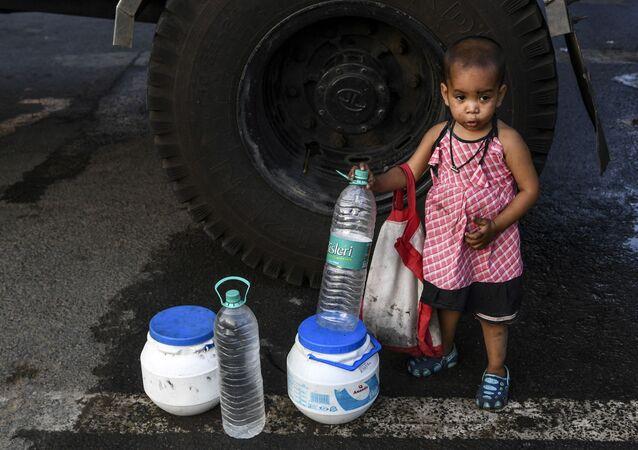 طفلة صغيرة تقف بجوار الزجاجات والعلب بينما تملأ والدتها بعضها بالمياه من صهريج توزيع المياه في نيودلهي بالهند حيث يواجه مئات الملايين صيفا لا يرحم يتميز بنقص حاد في المياه وتفاقم بسبب إغلاق فيروس كورونا المستجد، الهند، 20 مايو/ أيار 2020