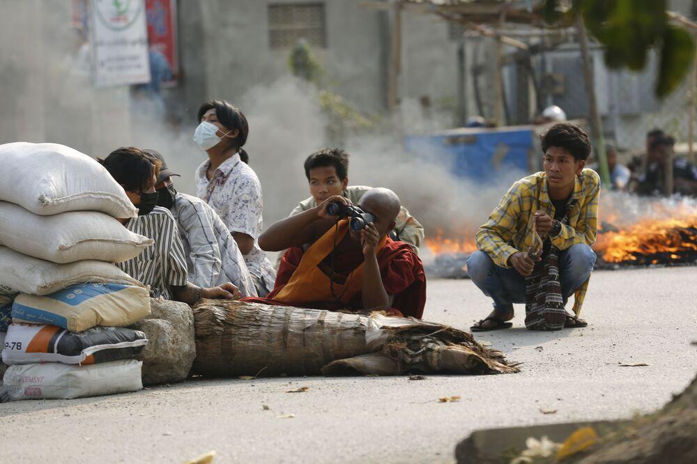 راهب بوذي يستخدم المنظار بينما يجلس مع رجال آخرين خلف حاجز طريق في ماندالاي، مع استمرار الاحتجاجات في ميانمار، 22 مارس 2021