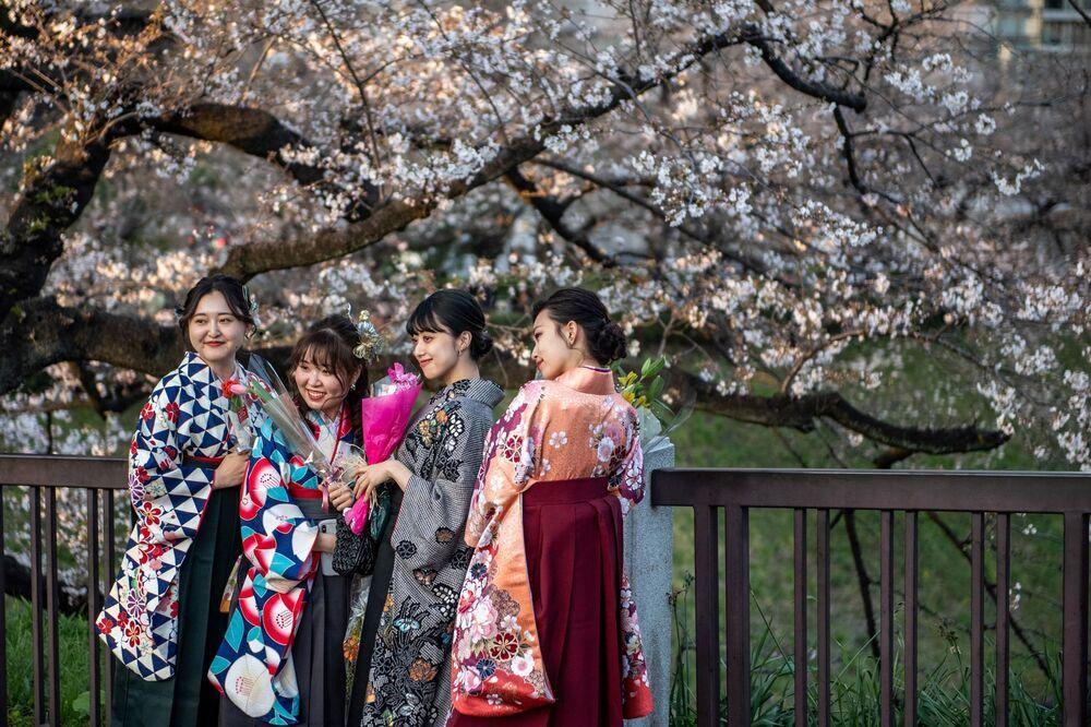 فتيات ترتدي الزي التقليدي هاكاما لحفلات التخرج من الجامعة، يلتقطون صورًا تحت أزهار الكرز في حديقة كيتانومارو في طوكيو، اليابان 23 مارس 2021، حيث بدأ تفتح أشجار الكرز الشهيرة ساكورا في البلاد قبل أسبوعين تقريبًا من الموعد المحدد.
