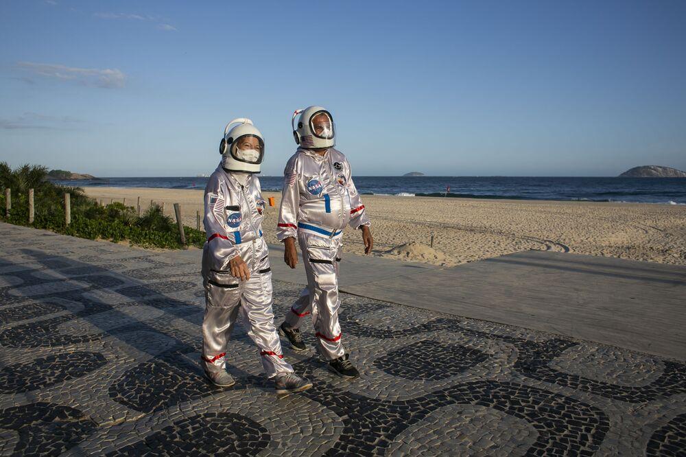 يسير المحاسب تيرسيو غالدينو وزوجته أليسيا، يرتديان ملابس رواد الفضاء، على طول شاطئ إيبانيما في ريو دي جانيرو، كوسيلة للحماية ضد الإصابة بالمرض الفيروسي كوفيد-19، على خلفية تزايد عدد حالات الإصابة في البرازيل، 20 مارس 2021