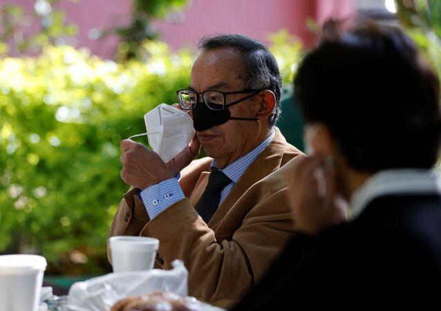 يظهر العالم المكسيكي غوستافو أكوستا ألتاميرانو مع ابتكاره الجديد، قناع الأنف كإجراء للحماية من انتقال مرض فيروس كورونا (كوفيد-19) أثناء عملية الأكل والشرب في المعهد الوطني للفنون التطبيقية، في مكسيكو سيتي، المكسيك، 18 مارس 2021