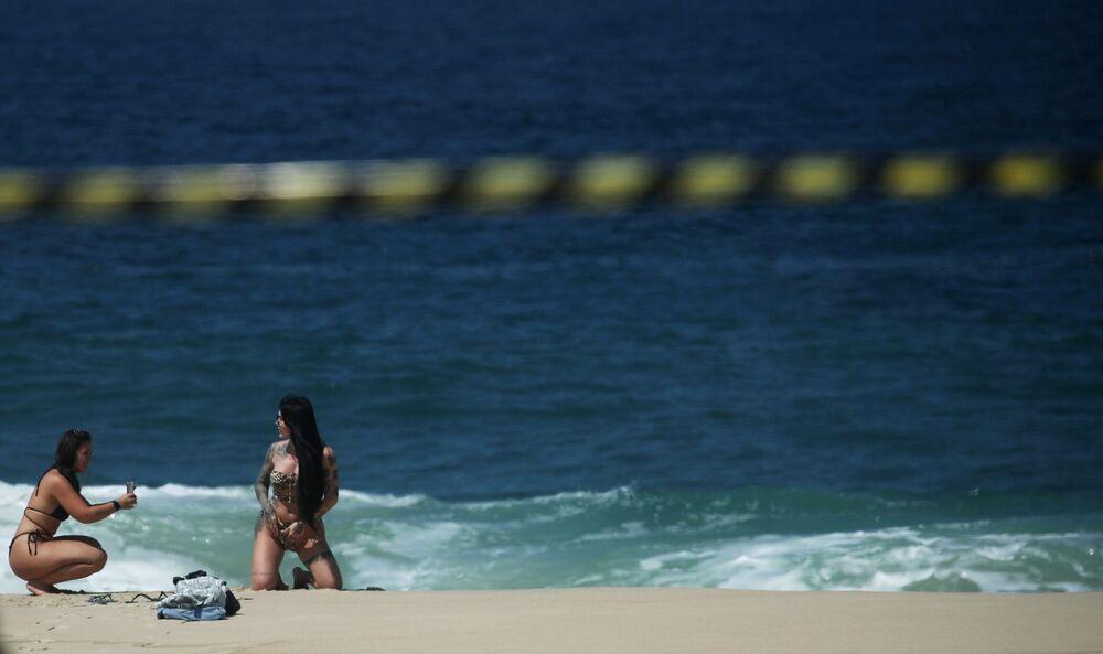 امرأة تقف على شاطئ إيبانيما، بعد إغلاق جميع الشواطئ كإجراء احترازي لاحتواء تفشي مرض فيروس كورونا (كوفيد-19) في ريو دي جانيرو، البرازيل، 20 مارس 2021