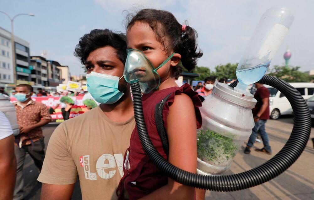 فتاة صغيرة ترتدي قناع الأكسجين لإثبات إمكانية ضخ الأكسجين من شجرة في زجاجة في المستقبل، خلال احتجاج ضد ممارسات الحكومة لإزالة الغابات في غابات الحياة البرية الرئيسية في سريلانكا من أجل التطورات الحديثة في كولومبو، سريلانكا، 22 مارس 2021