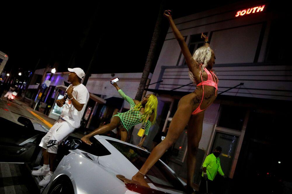 نساء يرقصن فوق سيارة بينما يستمتع المحتفلون بعطلة الربيع، على الرغم من حظر التجول الذي فرضته السلطات المحلية بدءاً من الساعة 8 مساءً، كإجراء احترازي للحد من تفشي جائحة فيروس كورونا (كوفيد-19) في ميامي بيتش، فلوريدا، الولايات المتحدة، 20 مارس 2021