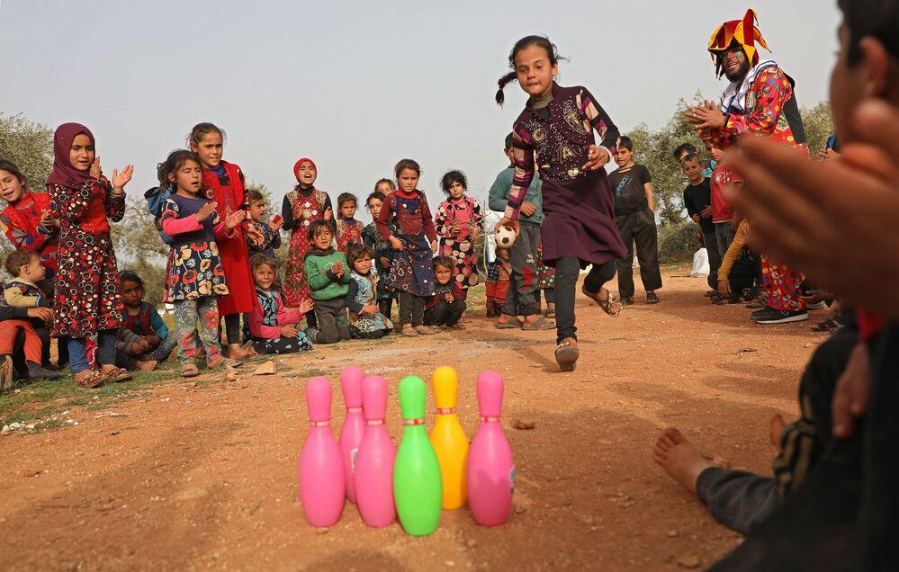أطفال يلعبون خلال عرض الكوميدي السوري فراس الأحمد (يظهر على يمين الصورة)، ويرتدي زي مهرج للترفيه عن الأطفال في الساحة الرئيسية لمخيم كفر جالس للنازحين في شمال إدلب، شمال غرب سوريا، 22 مارس2021