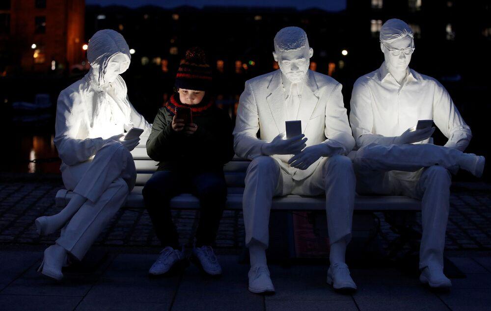 صبي يجلس على تمثال على شكل مقعدعليه أشخاص ينظرون إلى هواتفهم المحمولة، وهو يجلس بجوار جزء من تمثال مضاء الممتص من قبل الإضاءة، للفنان غالي ماي لوكاس، في ليفربول، بريطانيا، 22 مارس 2021