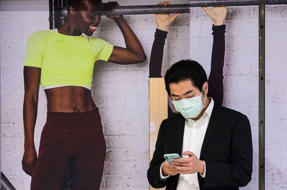رجل يستخدم هاتفه المحمول على خلفية صور كرتونية على هئية أشخاص في هونغ كونغ، 22 مارس 2021