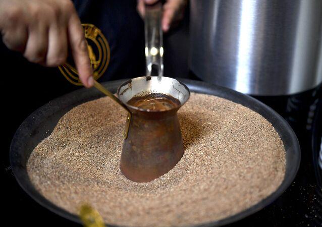 يقوم صانع القهوة المكسيكي بإعداد قهوة تركية مصنوعة داخل وعاء نحاسي على الرمال الساخنة أثناء افتتاح مهرجان القهوة إكسبو-كافيه 2017، بنسخته الـ 20 في مدينة مكسيكو سيتي، المكسيك،31 أغسطس 2017