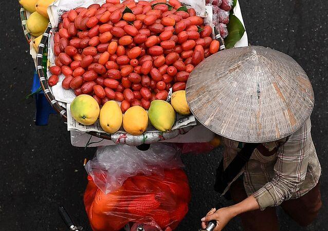 بائع متجول يحمل الفاكهة على دراجته في أحد شوارع مدينة هانوي، فيتنام 18 مارس 2021