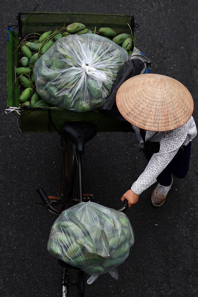 بائع متجول يحمل المانغو على دراجته في أحد شوارع مدينة هانوي، فيتنام 18 مارس 2021
