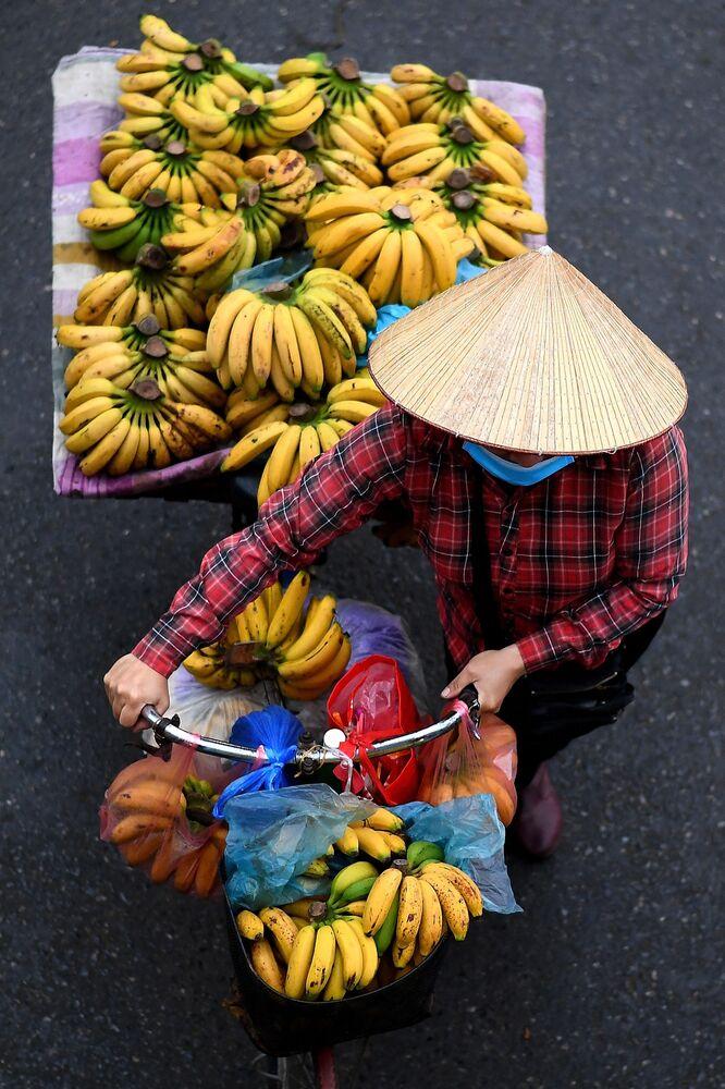 بائع متجول يحمل الموز على دراجته في أحد شوارع مدينة هانوي، فيتنام 18 مارس 2021