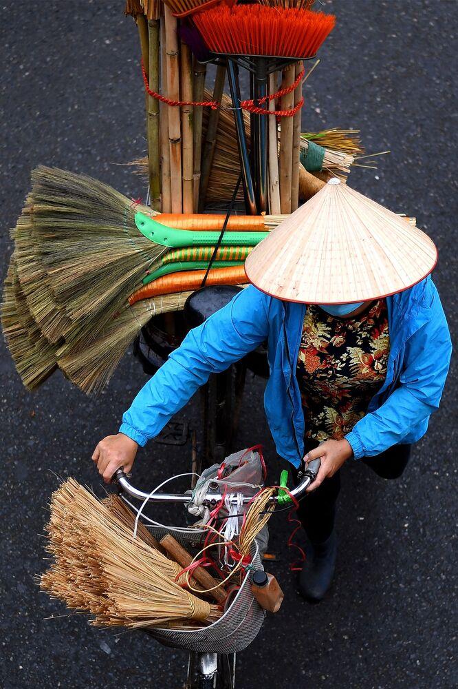 بائع متجول يحمل أعواد مكنسة على دراجته في أحد شوارع مدينة هانوي، فيتنام 18 مارس 2021
