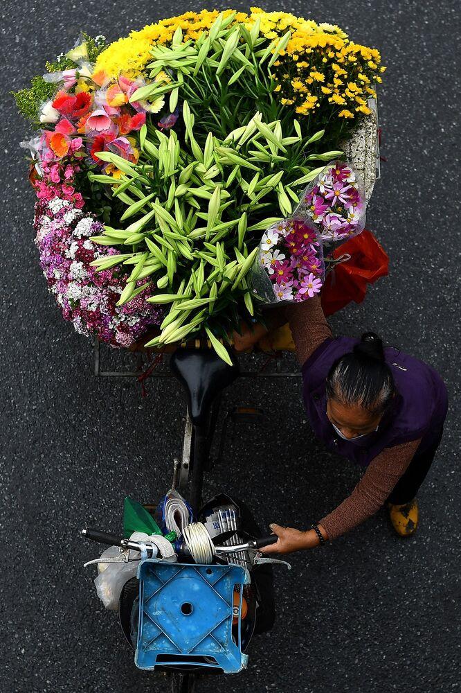 بائع متجول يحمل الأزهار على دراجته في أحد شوارع مدينة هانوي، فيتنام 18 مارس 2021