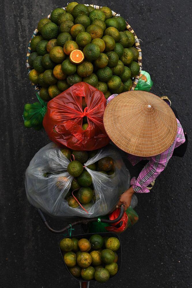 بائع متجول يحمل البرتقال على دراجته في أحد شوارع مدينة هانوي، فيتنام 18 مارس 2021