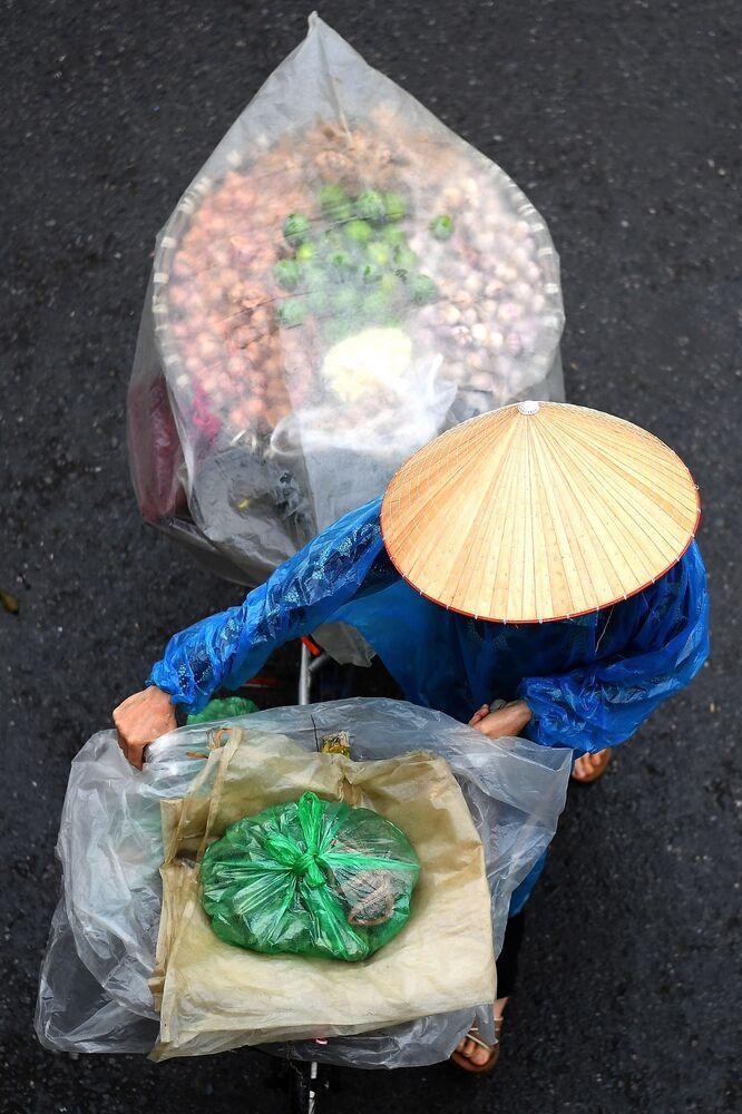 بائع متجول يحمل الخضار على دراجته في أحد شوارع مدينة هانوي، فيتنام 18 مارس 2021