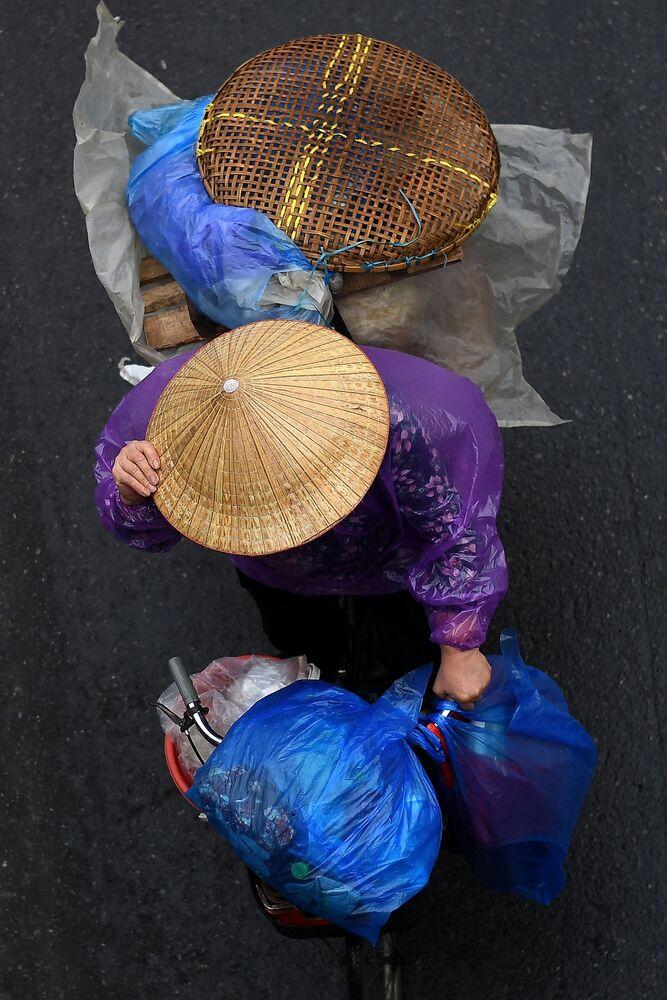 بائع متجول يحمل الأغراض على دراجته في أحد شوارع مدينة هانوي، فيتنام 18 مارس 2021