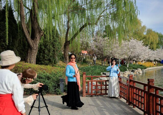 نساء يلتقطن صورا على خلفية تفتح أزهار شجر الكرز الشهيرة في هذا الوقت من العام، بكين، الصين 31 مارس 2021
