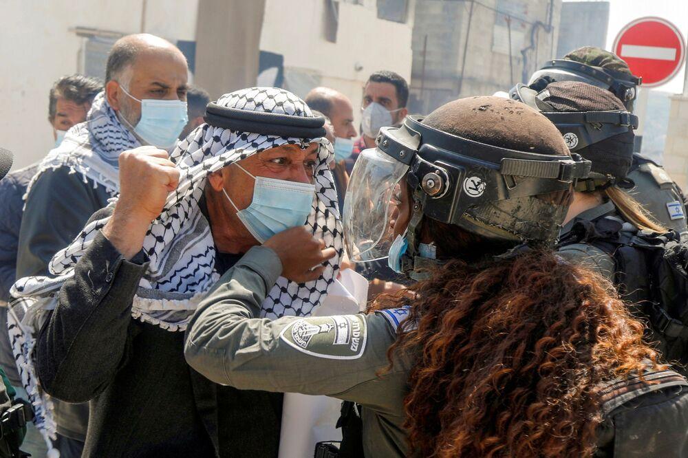 متظاهر فلسطيني يشتبك مع شرطية حدود إسرائيلية خلال مسيرة يوم الأرض، في سبسطية بالقرب من نابلس، في الضفة الغربية،  في 30 مارس 2021