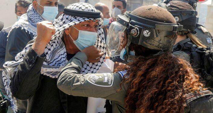 متظاهر فلسطيني يشتبك مع شرطية حدود إسرائيلية خلال عرض يوم الأرض ، في سبسطية بالقرب من نابلس ، في الضفة الغربية ، 30 مارس ، 2021
