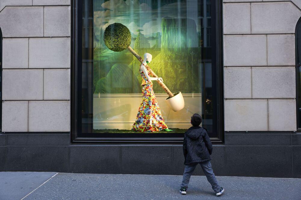توقف طفل لإلقاء نظرة على نافذة متجر بلومينغديلز في حي مانهاتن بمدينة نيويورك، نيويورك، الولايات المتحدة، 29 مارس 2021