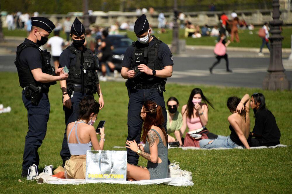ضباط الشرطة يتفقدون هوبات الأشخاص الذين يستمتعون بيوم ربيعي مشمس على العشب، أمام فندق des Invalides في باريس، وسط استمرار انتشار فيروس كورونا، 31 مارس 2021