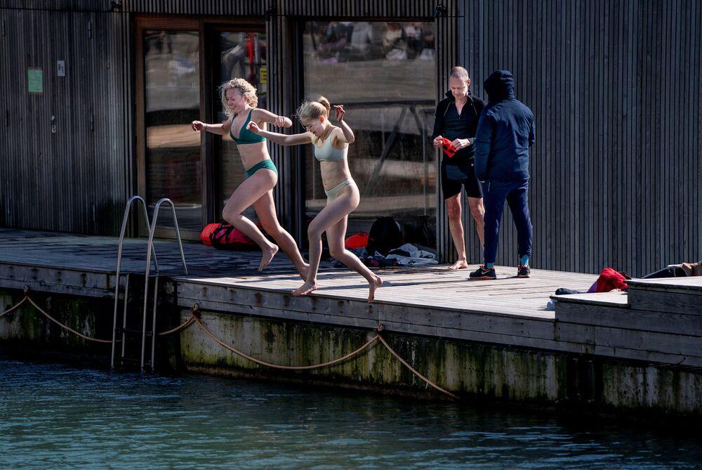 امرأتان تقفزان إلى بركة مياه  في منطقة ساندكاز هافنباد المخصصة للسباحة والاستجمام  كوبنهاغن، الدنمارك 30 مارس 2021