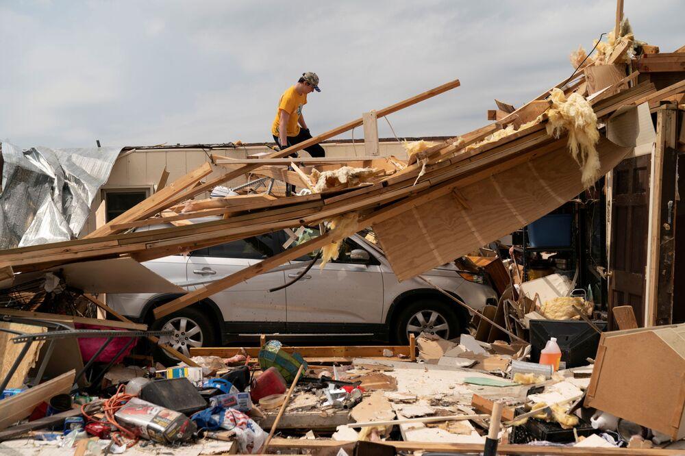 شاب يقيم الأضرار التي لحقت بمنزل جدته في اليوم التالي بعد سلسلة من الأعاصير التي أدت إلى مقتل الكثير من أهالي المنطقة في أوهاتشي، ألاباما، الولايات المتحدة، 26 مارس 2021.