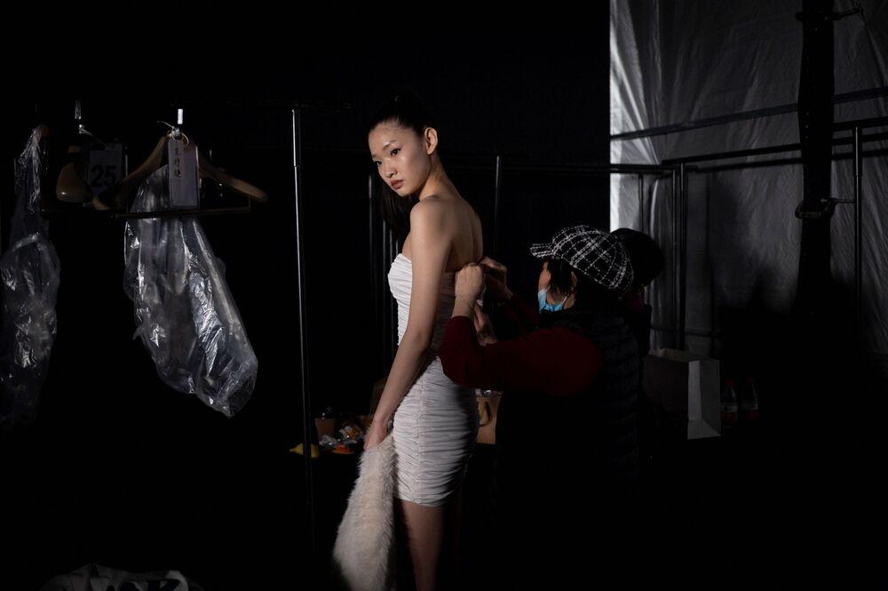 عارضة أزياء خلف الكواليس أثناء التجهيزات ووضع اللمسات الأخيرة قبل الخروج على منصة العرض بيوتي بيري من المصمم وانغ يوتو، في إطار أسبوع الموضة الصيني في بكين، الصين 28 مارس 2021