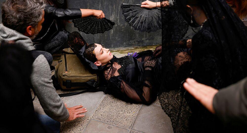 عارضة أزياء مستلقية على الأرض بعد أن عانت من الدوار في الرأس، قبل بدء عرض أزياء المانتيلا التقليدية التي ابتكرها مصممون مختلفين، وسط قيود بسبب جائحة فيروس كورونا (كوفيد-19) في إشبيلية، إسبانيا في 26 مارس 2021