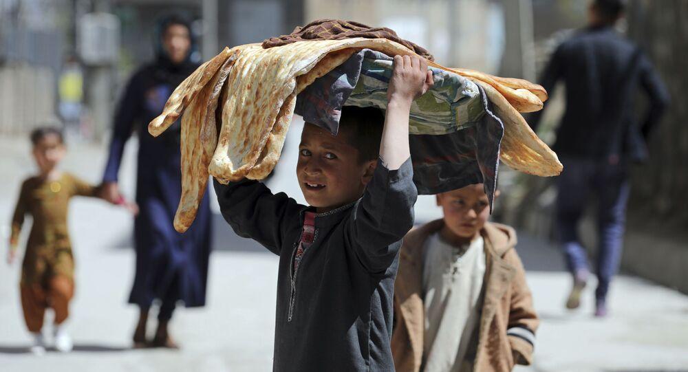 طفل أفغاني يحمل الخبز على رأسه في كابول، أفغانستان 29 مارس 2021
