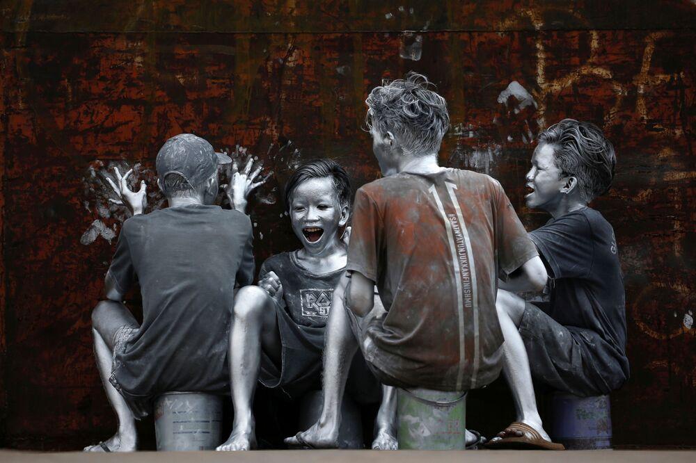 الشباب، الذين غطوا أنفسهم من الرأس إلى أخمص القدمين بالطلاء الفضي ليصبحوا فضية مانوسيا (الرجال الفضيون)، في إطار فعالية لجذب الانتباه إليهم وكجزء من عملهم لكسب الرزق خاصة بعد تدهور الوضع الاقتصادي بسبب الجائحة، يضحكون وهم يركبون شاحنة في جاكرتا، إندونيسيا 31 مارس  2021