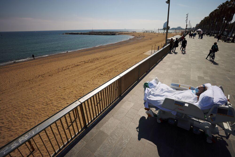 المريض جوان سولير سيندرا، 63 عامًا، وهو أصم وبكم، ينظر إلى البحر بجوارالأطباء (الذين يقفون خلف الصورة) كجزء من جلسة العلاج البحري، بعد 114 يومًا من دخوله مستشفى ديل مار بسبب مرض فيروس كورونا ( كوفيد-19) في برشلونة، إسبانيا، 25 مارس 2021