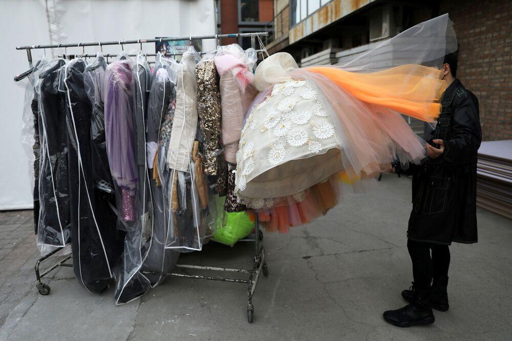 رجل يفرز تصميمام المصمم على علاقة ملابس خارج مكان لعرض الأزياء، ي إار أسبوع الموضة في بكين، الصين، 30 مارس 2021