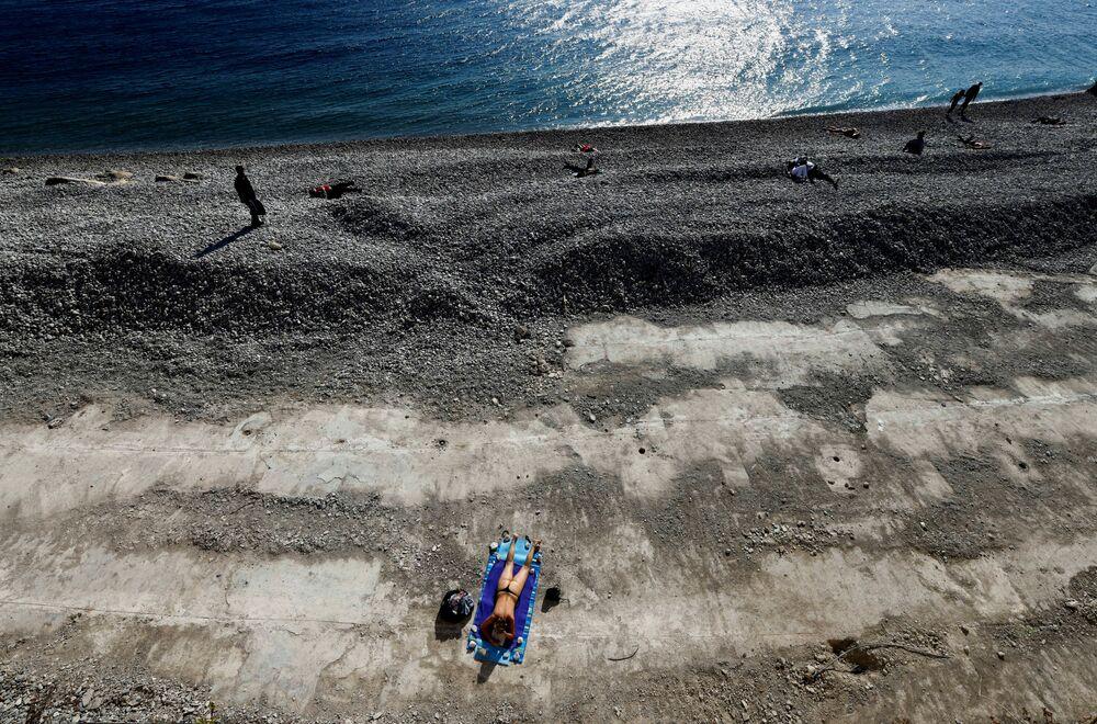 امرأة تستجم على شاطئ بروميناد ديزونغليه، خلال الإغلاق العام الثالث المفروض لإبطاء معدل الإصابة بمرض فيروس كورونا (كوفيد-19) في نيس، فرنسا 27 مارس 2021