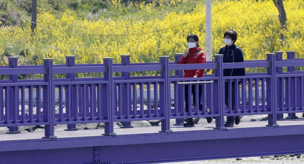 سياح يسيرون على الجسر البنفسجي (جسر الملاك) الذي يربط جزيرتي بانفول وباركجي في محافظة تشلا الجنوبية في كوريا الجنوبية، 6 أبريل 2021