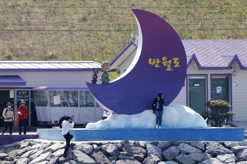 سياح يلتقطون صوراً على خلفية شعار الجزر البنفجسية في محافظة تشلا الجنوبية في كوريا الجنوبية، 6 أبريل 2021