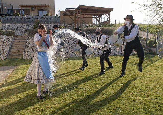 حبس التقليد المجري القديم، في يوم الاثنين بعد عيد الفصح يرتدي الأهالي الأزياء الشعبية، ويقوم الشباب، أعضاء جمعية ماركال للرقص والفنون الشعبية، بصب الماء على الفتيات الشابات، في مينفوكساناك، المجر، 5 أبريل 2021.