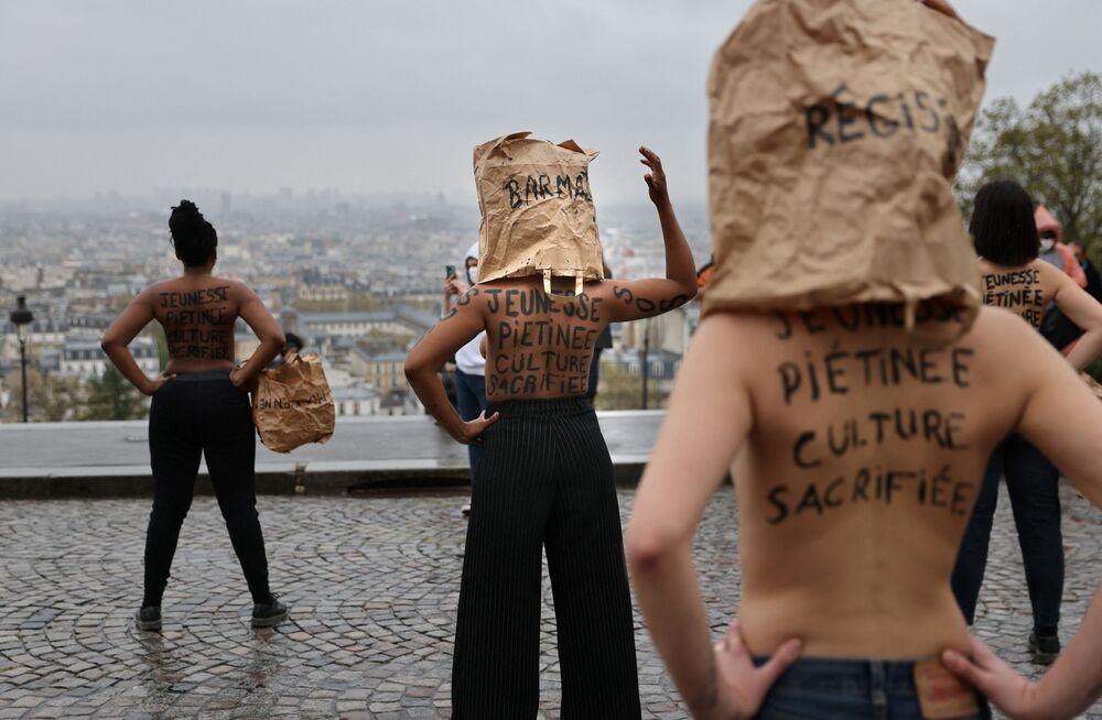 متظاهرون يعبرون عن احتجاجهم ضد إغلاق متاجر التجزئة غير الضرورية، أمام كاتدرائية ساكري كور في باريس، في 5 أبريل 2021