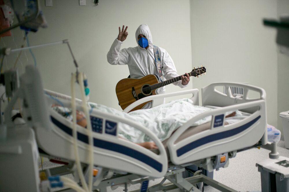موظف في الرعاية الصحية في المستشفى الخيري البرتغالي في بيليم، ولاية بارا، البرازيل، يغني ويصلي من أجل مريض مصاب بـ كوفيد -19 داخل أجنحة المستشفى ومناطق العناية المركزة كجزء من احتفالات عيد الفصح، في 4 أبريل 2021.