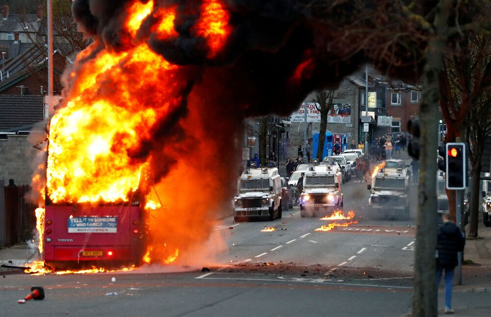 سيارات الشرطة تظهر خلف حافلة مخطوفة تحترق على طريق شانكيلЛ مع استمرار الاحتجاجات في بلفاست، أيرلندا الشمالية، 7 أبريل 2021