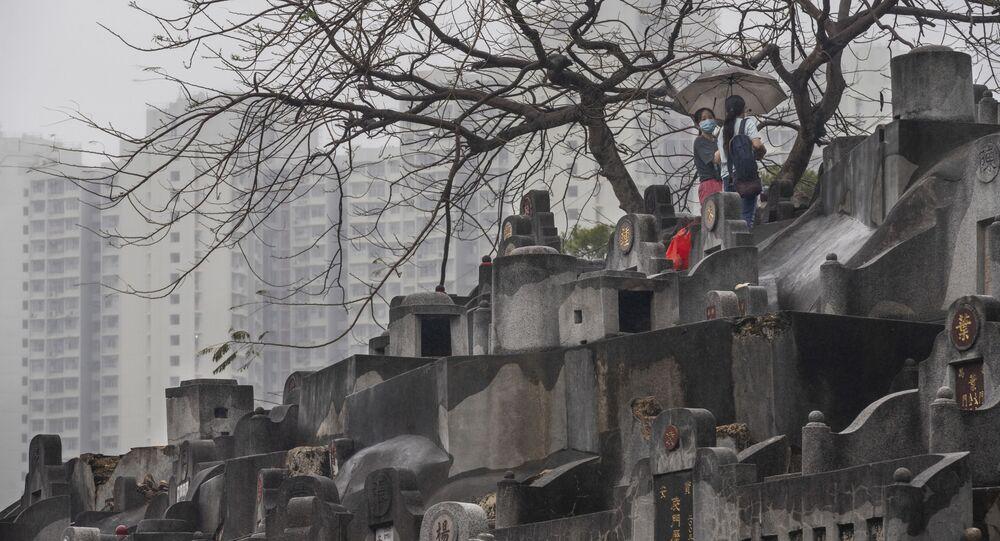 نساء يصلين في مقبرة خلال مهرجان تشينغ مينغ، حيث تظهر المباني السكنية العامة في الخلفية في هونغ كونغ، الصين.