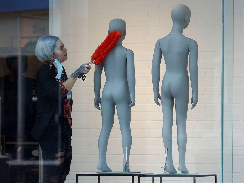 موظفة تقوم بتنظيف نافذة عرض في متجر لبيع الملابس قبل إعادة الافتتاح المقرر الأسبوع المقبل، وسط تفشي فيروس كورونا (كوفيد-19) في ليفربول، بريطانيا، 7 أبريل 2021