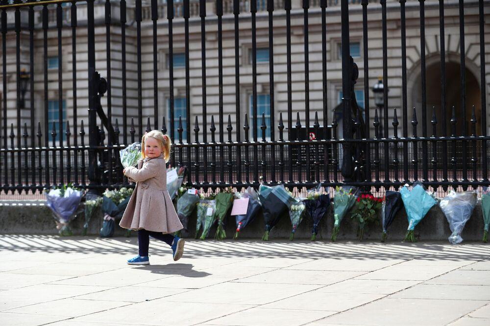 طفلة صغيرة، ماغي (عامين)، تحمل باقة من الورود لوضعها أمام قصر باكنغهام، بعد الإعلان رسميا عن وفاة  الأمير فيليب زوج ملكة بريطانيا إليزابيث الثانية، لندن، بريطانيا 9 أبريل 2021