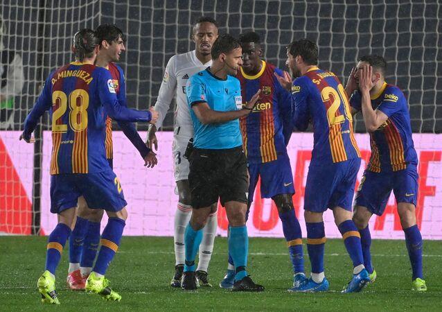 لاعبو برشلونة يطالبون حكم المباراة الكلاسيكو باحتساب ركلة جزاء لهم خلال مباراة ريال مدريد