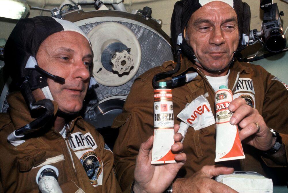 رائدا الفضاء الأمريكيان توماس ستافورد ودونالد كنت يمسكان أنابيب الطعام في مركبة الفضاء السوفيتية سويوز