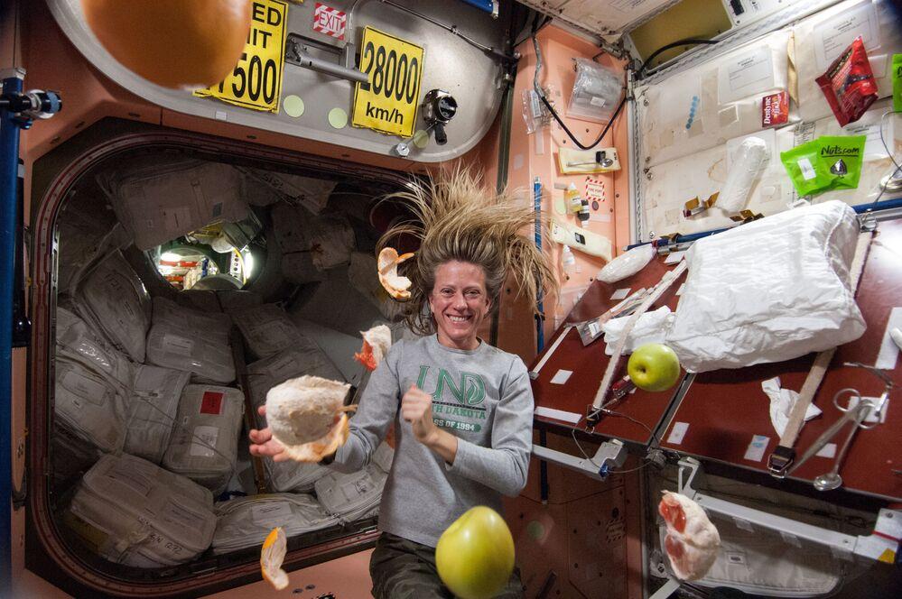 رائدة فضاء ناسا كارين نيبيرج، مهندسة رحلة لبعثة رقم 36، تظهر بالقرب من فاكهة طازجة تطفو بحرية في محطة الفضاء الدولية.