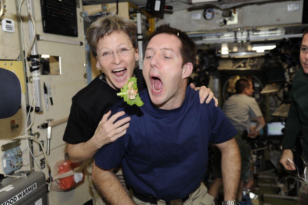 رائد الفضاء الفرنسي توما بيسشي، ورائدة الفضاء في ناسا بيجي ويتسون، يأكلان الخس الذي تم زراعته على متن محطة الفضاء الدولية