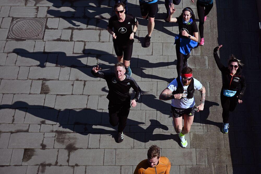 أشخاص يافعون خلال رياضة الركض على ضفة نهر موسكو، روسيا 11 أبريل 2021